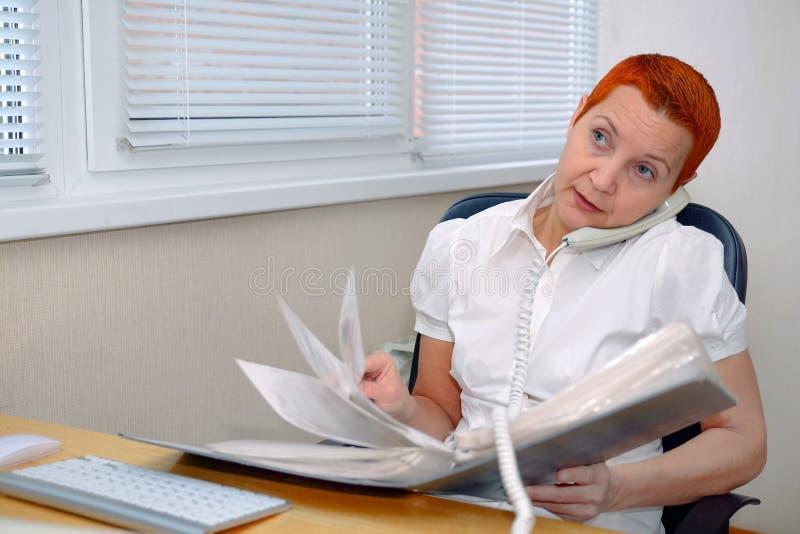 Kijkend door de documenten, de Manager die van het meisjesbureau op de telefoon spreken stock afbeelding