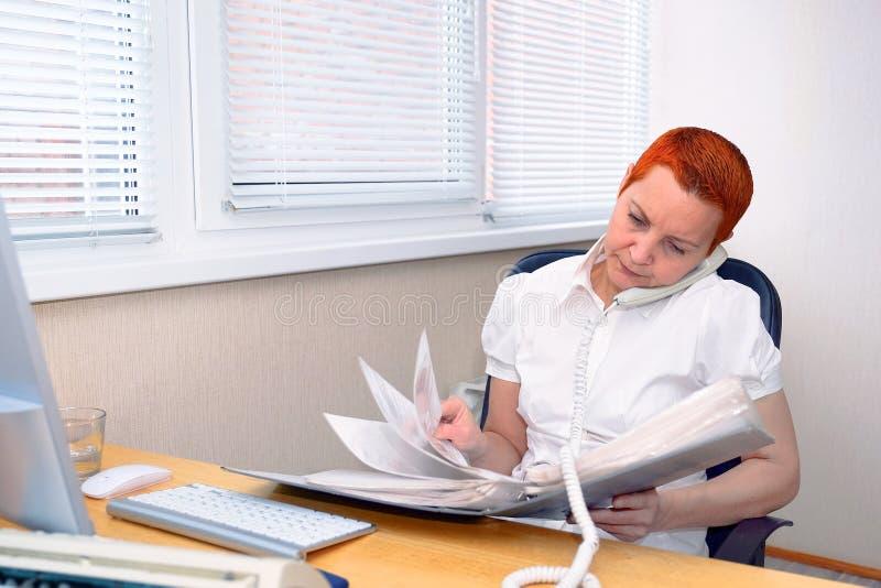 Kijkend door de documenten, de Manager die van het meisjesbureau op de telefoon spreken royalty-vrije stock foto's
