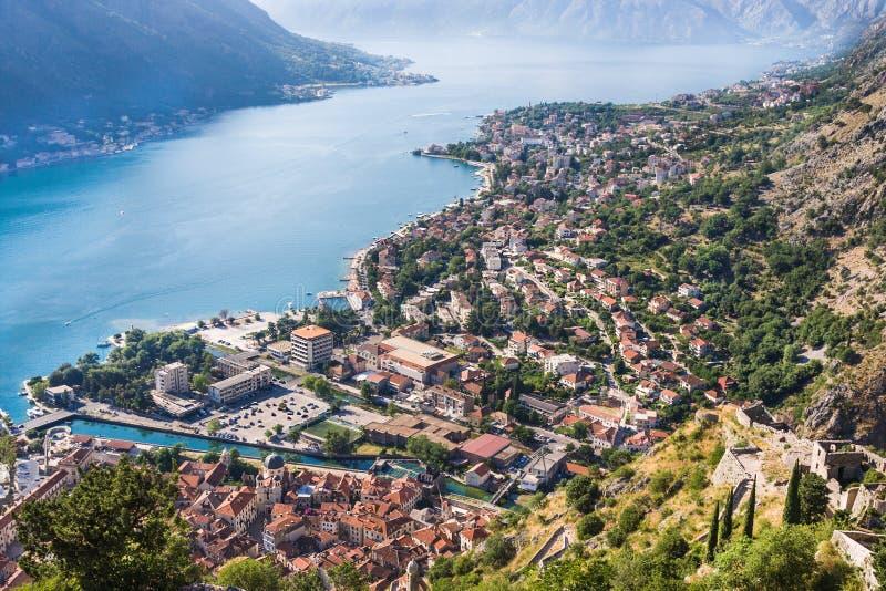 Kijkend over de Baai van Kotor in Montenegro met mening van bergen, boten en oude huizen met rode tegeldaken stock fotografie
