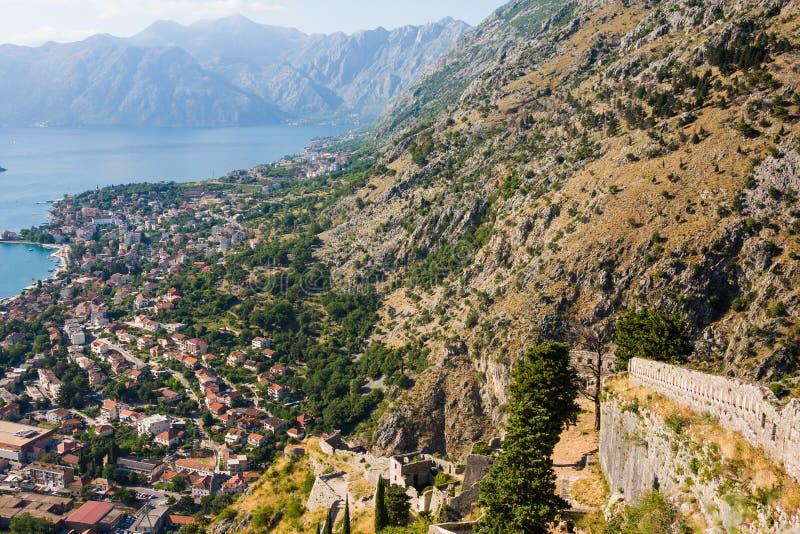 Kijkend over de Baai van Kotor in Montenegro met mening van bergen, boten en oude huizen met rode tegeldaken stock afbeeldingen