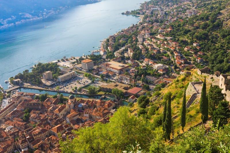 Kijkend over de Baai van Kotor in Montenegro met mening van bergen, boten en oude huizen met rode tegeldaken royalty-vrije stock foto