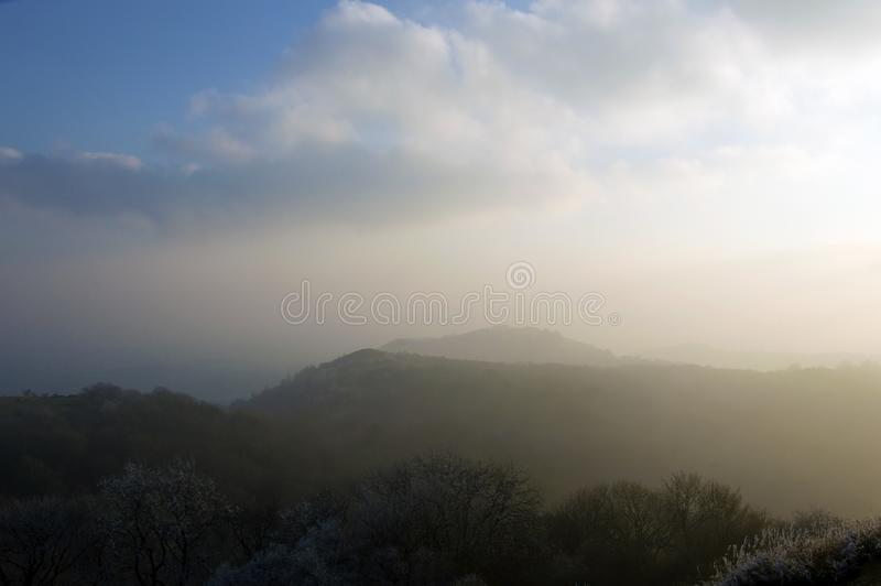 Kijkend over de rand en de bossen van de Malvern-Heuvels op een koude, ijzige, nevelige middag Worcestershire, het UK stock afbeeldingen