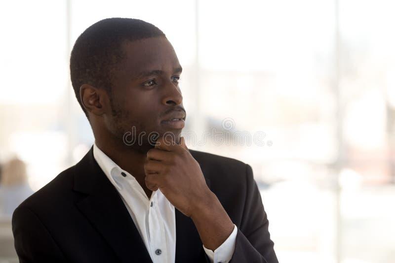 Kijkt de hoofd geschotene portret nadenkende Afrikaanse Amerikaanse zakenman in afstand royalty-vrije stock foto