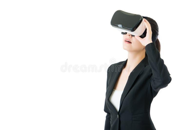 Kijkt de schoonheids Aziatische vrouw door VR-glazen voor zaken stock foto