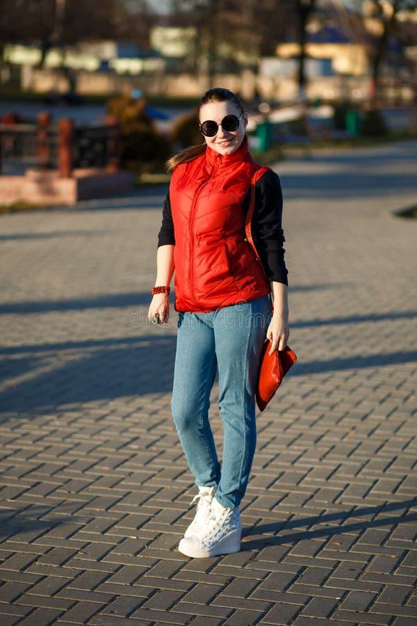Kijkt het manier mooie meisje met verzameld haar Zij draagt een rood vest en jeans, zijn handtas van de schouder rode manier royalty-vrije stock fotografie