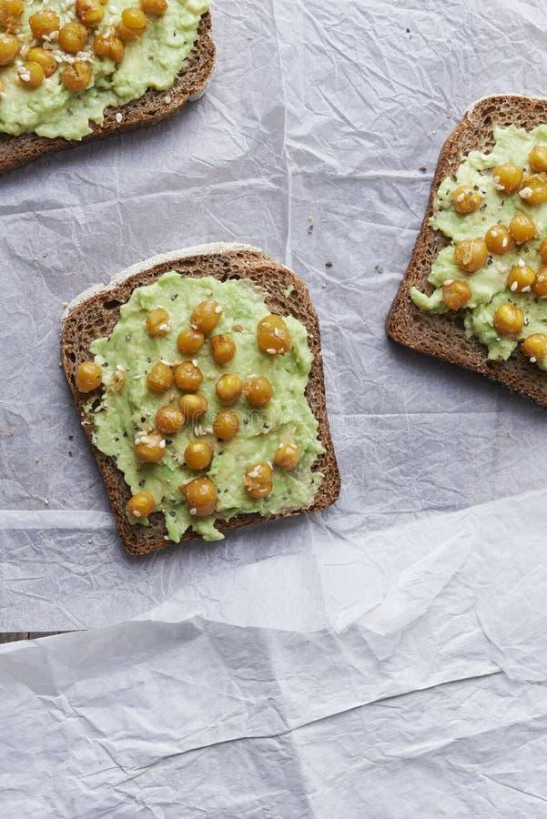 Kikärt- och avokadorostat bröd med sesam royaltyfri foto
