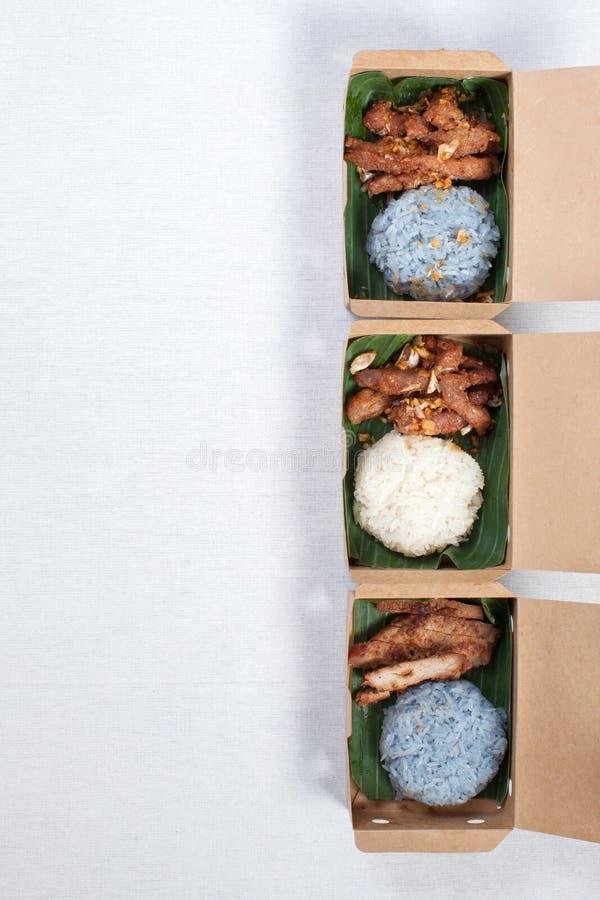 Kikkerrijst met gegrild varkensvlees en gefrituurd varkensvlees in een bruine papierdoos, op een witte tafellade, in een voedselb stock foto's