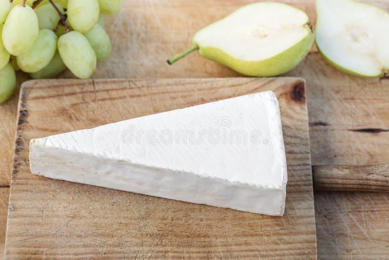 Kil av Brie på lantlig vit träbackeround vit s royaltyfria bilder