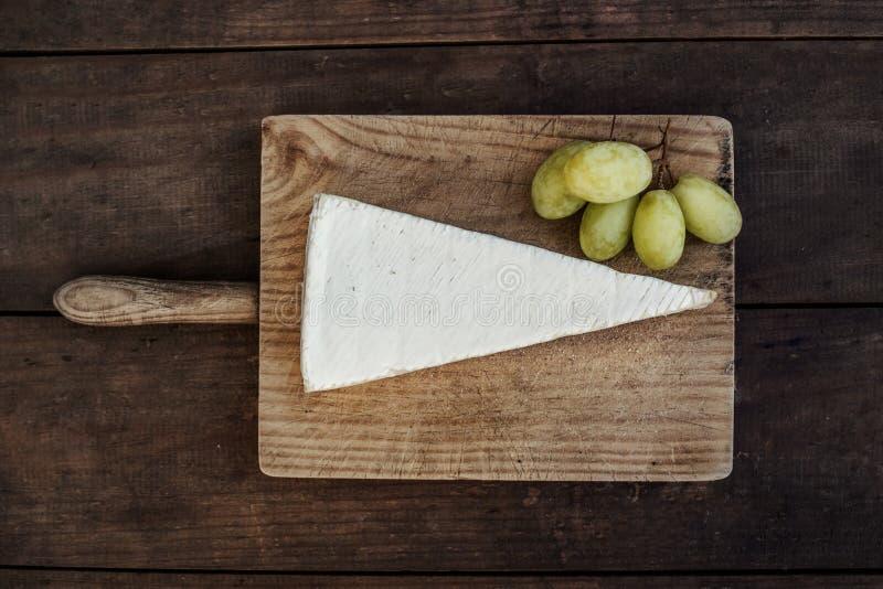 Kil av Brie på mörk träbakgrund Top beskådar snut arkivfoto