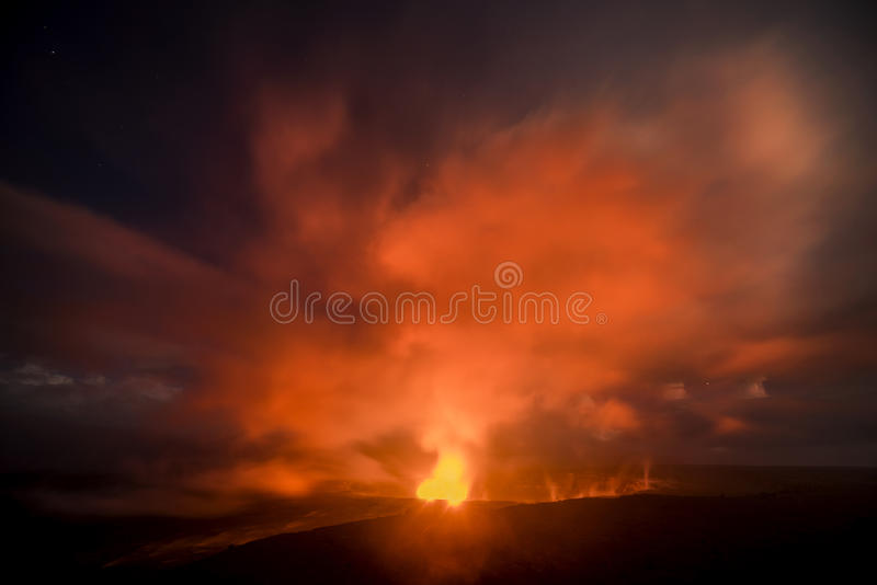 Kilauea Volcano at Night. A 30-second captures the glowing lava lake in the caldera of Hawaii`s Kilauea Volcano as it bounces light off of the haze drifting by royalty free stock photography