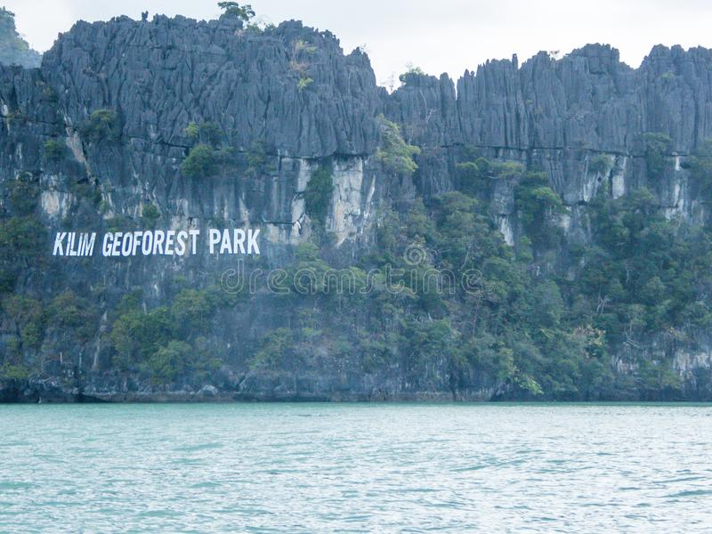 Malaysia - Kilim Geoforest Park. The Kilim Geoforset Park sign, seen from a boat. The sigh is situated on a mountain, rocky surface. Calm water washes the royalty free stock photos