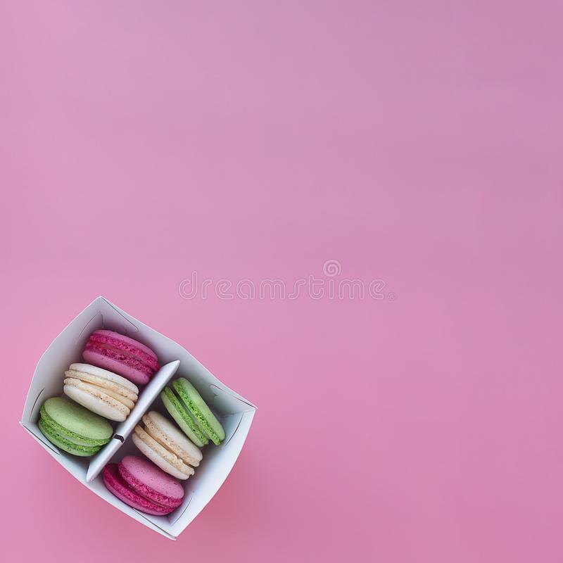 Kilka barwiący macarons w papierowym pudełku na obciosują różowego tło fotografia royalty free