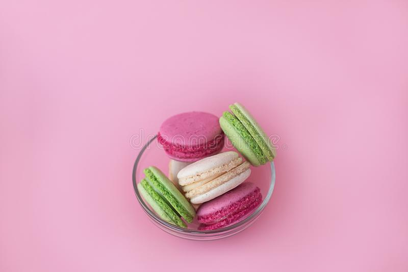 Kilka barwiący macarons w szklanym talerzu na różowym tle fotografia royalty free