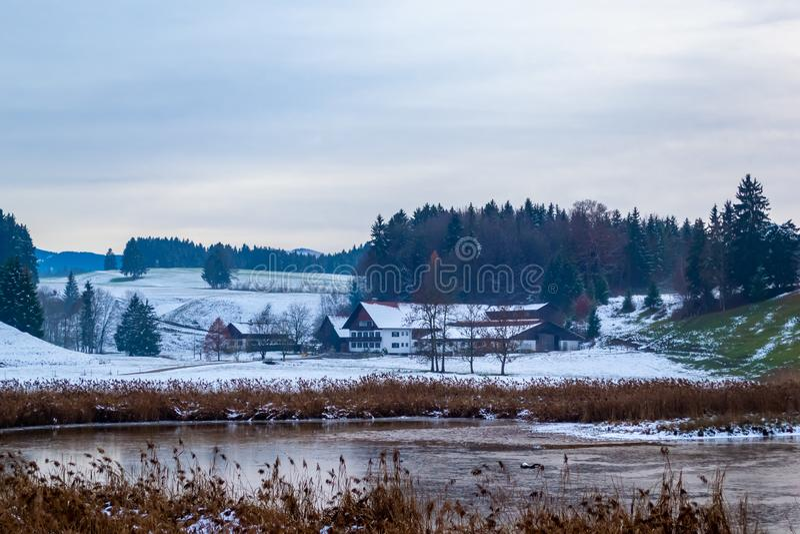 Kilka domy na jeziorze Zima czas, śnieg spadał Sosnowy las i g?ry obrazy stock