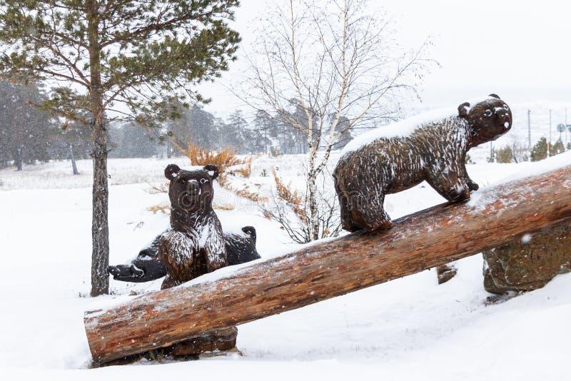 Kilka drewniani niedźwiedzie na nazwy użytkownikiej zimie Drewniana postać niedźwiedzie w w górę opad śniegu obrazy royalty free