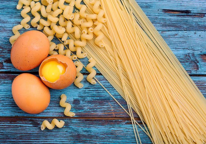 kilka jajka, mąka i spaghetti, kłamają na drewnianym stole obraz stock
