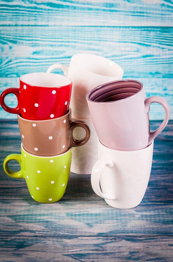 Kilka kolorowe herbaciane filiżanki na rocznika tle zdjęcie stock