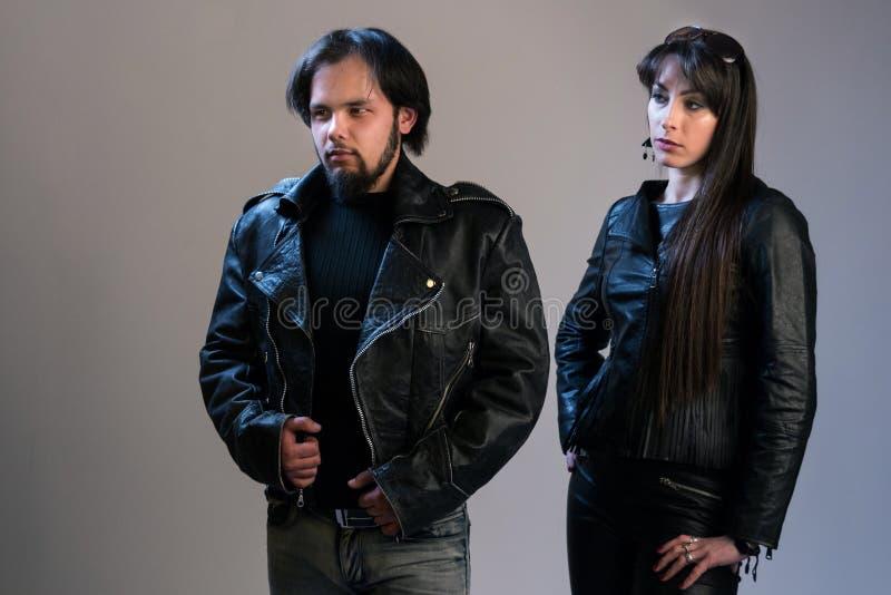 Kilka młodzi ludzie w czarnych skórzanych kurtkach Facet i dziewczyna w stylu pozuje w studiu bujaka lub rowerzysty obraz royalty free