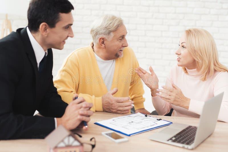 Kilka starzy ludzie przychodzili konsultacja z pośrednikiem handlu nieruchomościami Słuchają attentively everything który mówi po zdjęcie royalty free