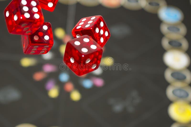 Kilka toczni czerwoni kostka do gry spadają na stole z boardgame Gameplay momenty fotografia stock