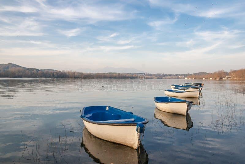 Kilka wioślarskie łodzie na spokojnym jeziorze z niebieskim niebem zdjęcie stock