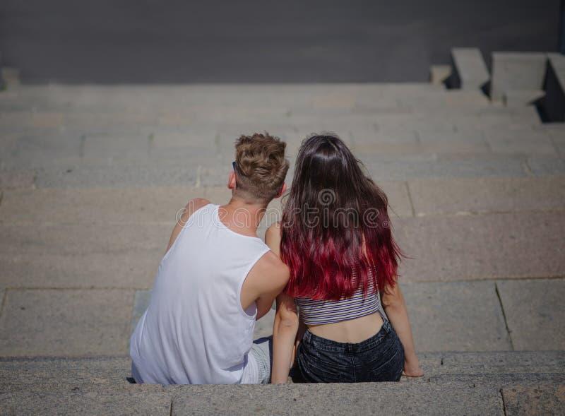 Kilka youngers siedzi i patrzeje w odległość na kamiennym schodka tle Relaks, romans, outdoors obraz stock