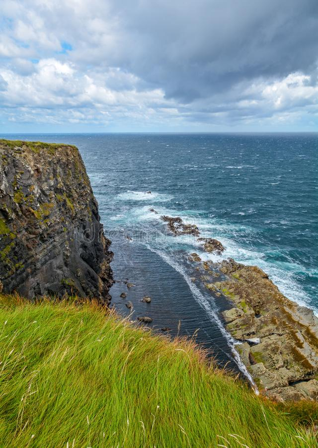 Cliffs and waves near Kilkee, County Clare, Ireland. Kilkee is a small coastal town in County Clare, Ireland. It is in the parish of Kilkee, formerly Kilfearagh royalty free stock image