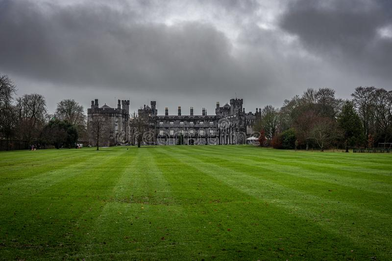 KILKENNY, IRELAND, DECEMBER 23, 2018: Kilkenny Castle seen from the huge garden on a dramatic cloudy day with dry leaves over the stock photos