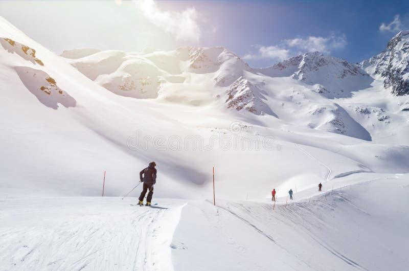 Kilku narciarzy biegnie po zboczu w pięknym zaśnieżonym krajobrazie górskim obraz royalty free