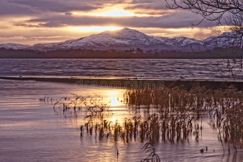 Killarney. Lake at sunrise with snow capped mountains in the distance royalty free stock photo