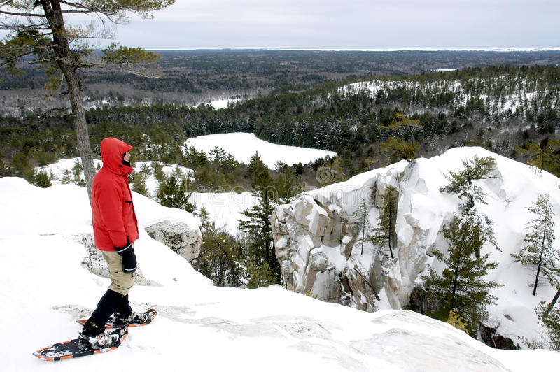 Killarney Provincial Park - Winter. A snowshoe enthusiast climbs to the top of The Crack on the South Ridge of the LaCloche Mountain range in Killarney royalty free stock images
