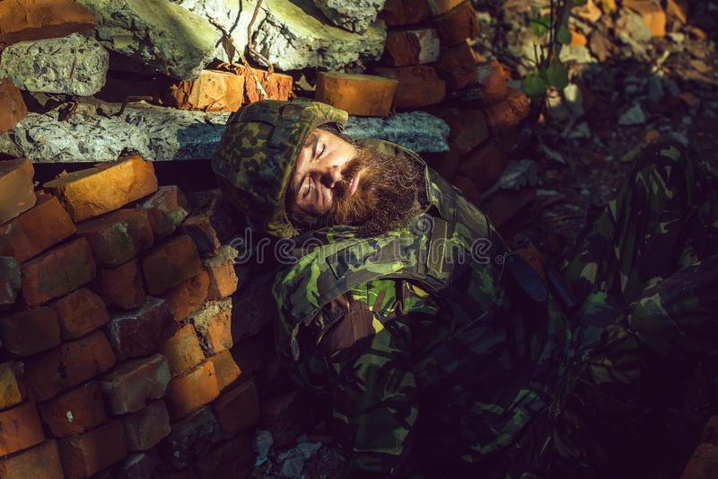 Killed soldier with beard on face in camouflage and military helmet on stone brick background. royalty free stock photography