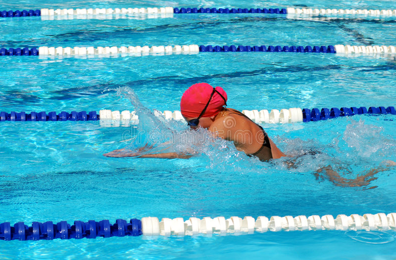 Killer breaststroke. Young girl at swim meet swimming breaststroke in the pool with pink swim cap royalty free stock images