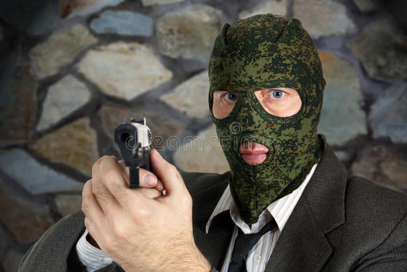 Killer in camouflage mask is aiming with a pistol. Killer in camouflage mask is aiming with the pistol stock images