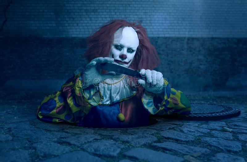 A killer clown with a knife rising from the sewer stock photo