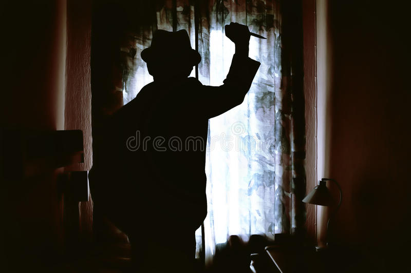 Killer's silhouette in a dark room royalty free stock images