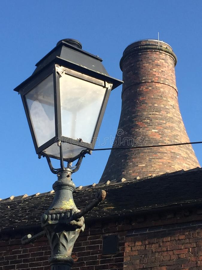 The kiln and the lamp - a romance. Lovely up-close shot of a bottle kiln from The Potteries, against a foreground of a decorative victorian lamp-post, covered in royalty free stock photos
