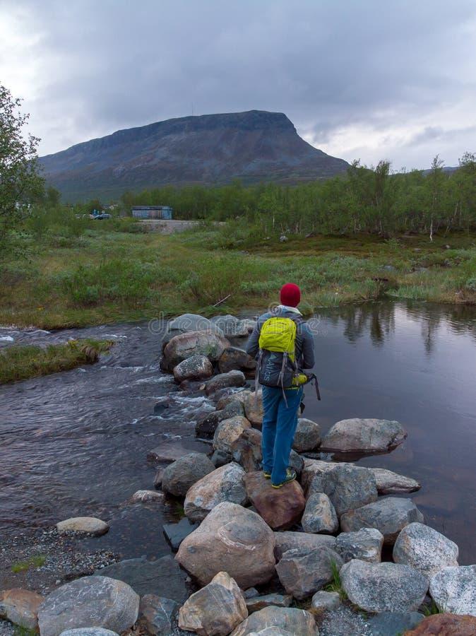 Kilpisjärvi, Finlandia - 27 de junho de 2018: Posição do homem sobre as rochas que vão através de um rio, com a montanha de Saan imagens de stock royalty free