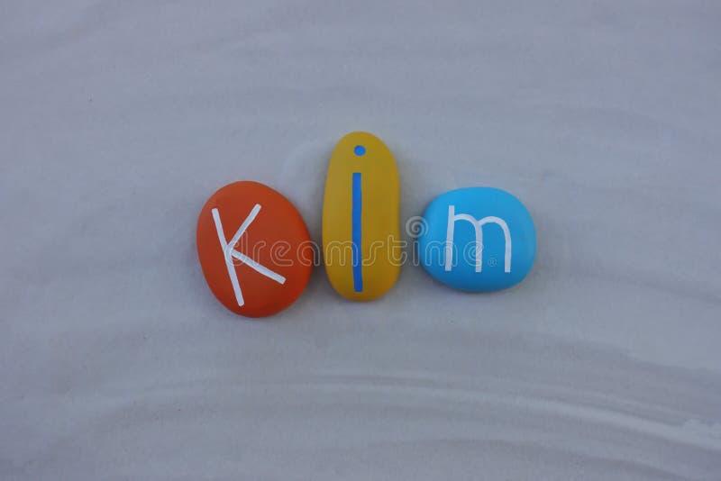 Kim, λαμβάνοντας υπόψη το όνομα που συντίθεται με τις χρωματισμένες πέτρες πέρα από την άσπρη άμμο στοκ φωτογραφίες με δικαίωμα ελεύθερης χρήσης