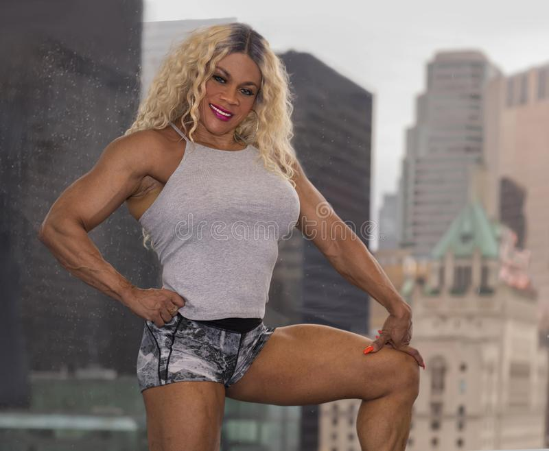 Kim Buck, Enticing Woman Bodybuilder. Sultry female professional bodybuilder Kim Buck from Georgia, pauses to pose with a window view of Toronto as a backdrop stock photos