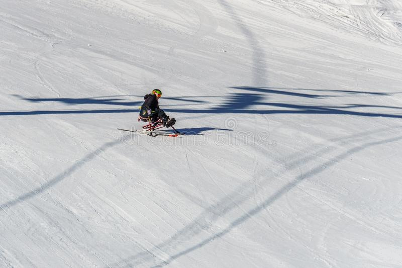 KIMBERLEY, CANADA - MAART 22, 2019: gehandicapte persoon die een Aanpassingssneeuwsporten berijden van zitten-skisvancouver stock afbeelding