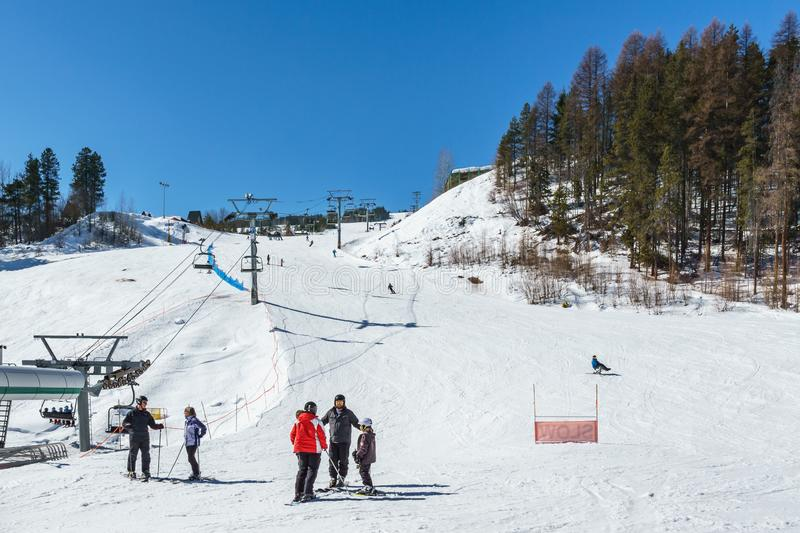 KIMBERLEY, CANADA - MARCH 19, 2019: ski track at alpine resort at sunny spring day. Blue cable chair high hill landscape lift mountain nature people recreation stock photo