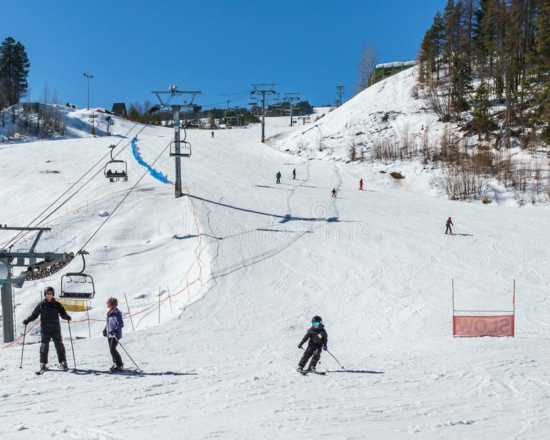 KIMBERLEY, CANADA - MARCH 19, 2019: ski track at alpine resort at sunny spring day. Blue cable chair high hill landscape lift mountain nature people recreation stock photography