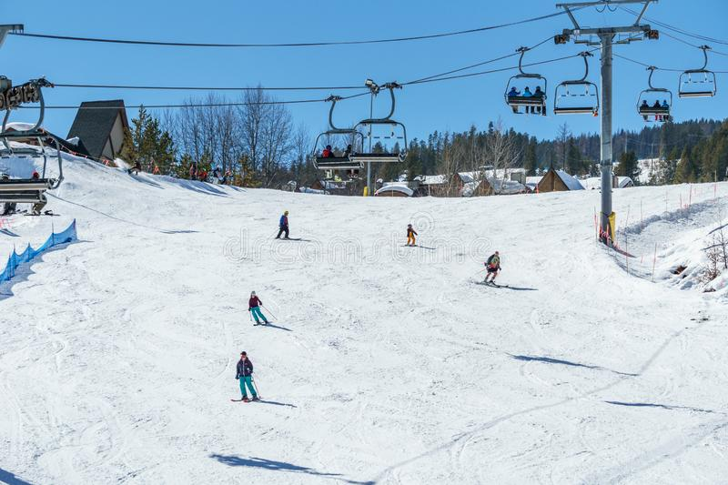 KIMBERLEY, CANADA - MARCH 19, 2019: ski track at alpine resort at sunny spring day. Blue cable chair high hill landscape lift mountain nature people recreation royalty free stock images