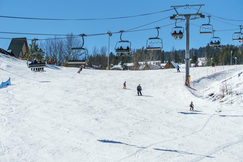 KIMBERLEY, CANADA - MARCH 19, 2019: ski track at alpine resort at sunny spring day. Blue cable chair high hill landscape lift mountain nature people recreation royalty free stock photography