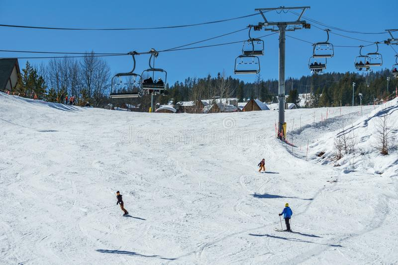 KIMBERLEY, CANADA - MARCH 19, 2019: ski track at alpine resort at sunny spring day. Blue cable chair high hill landscape lift mountain nature people recreation royalty free stock photo