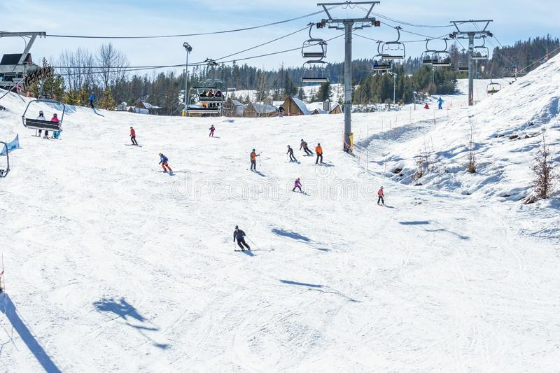 KIMBERLEY, CANADA - MARCH 19, 2019: ski track at alpine resort at sunny spring day. Blue cable chair high hill landscape lift mountain nature people recreation stock photos