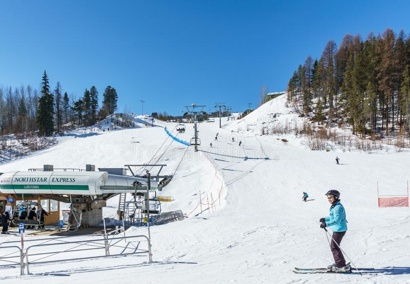 KIMBERLEY, CANADA - MARCH 19, 2019: ski track at alpine resort at sunny spring day. Blue cable chair high hill landscape lift mountain nature people recreation royalty free stock photos