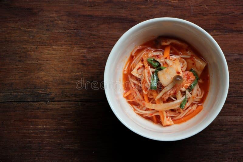 Kimchi épicé de champignon dans une cuvette sur le fond en bois photos libres de droits