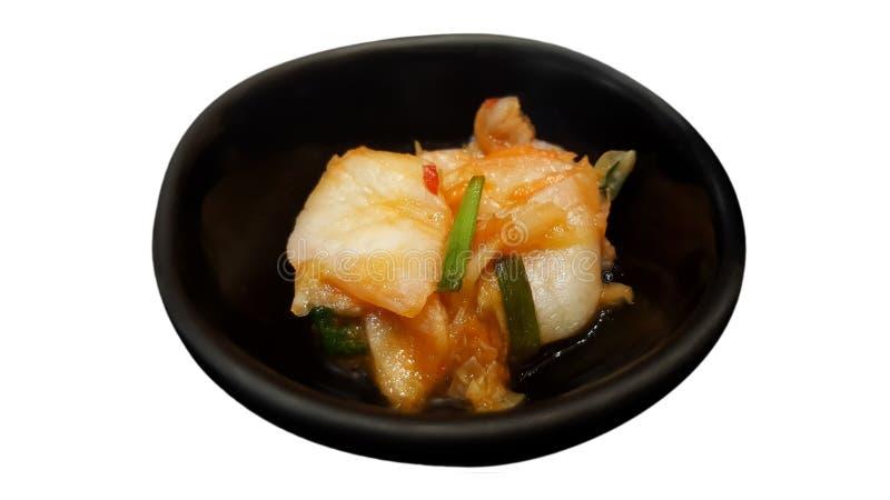 Kimchi en la placa negra aislada en fondo con la trayectoria de recortes imagen de archivo